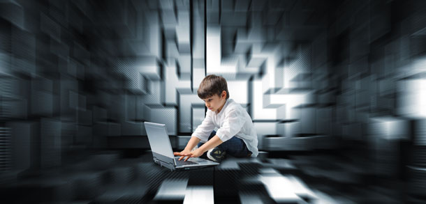 Boy sat cross-legged in front of a laptop