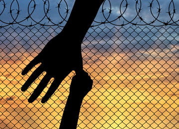 Child's hand holding on to thumb of adult hand with fence, barbed wire and sunset in the background