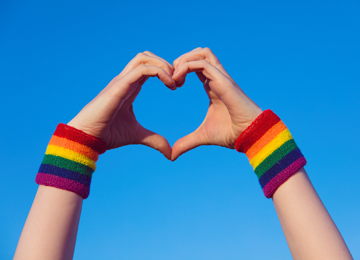 Hands with rainbow coloured wristbands creating a heart with a blue background