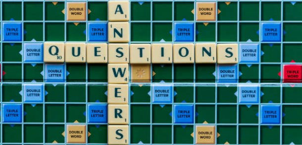 A scrabble board with letters on it that spell out questions across and answers down.