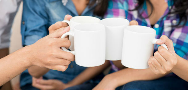 Four women sit and clink their tea mugs together