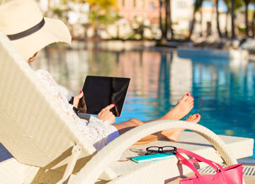 Woman using a tablet by a swimming pool