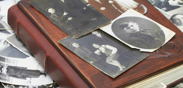 Old black and white photographs lie on top of an old book