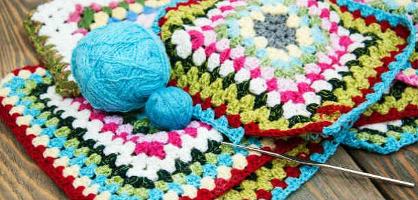 Multi-coloured crochet squares with two balls of wool and a crochet hook.