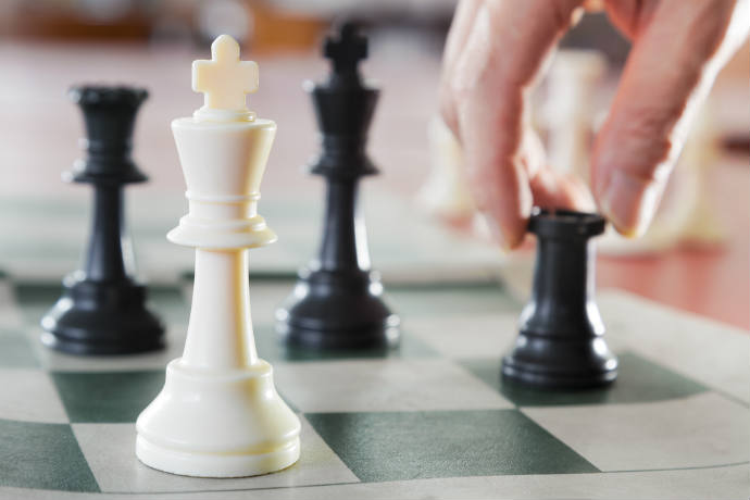 A hand moves a black rook chess piece next to a queen and two kings.