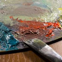 Oil paints on a palette with paintbrush