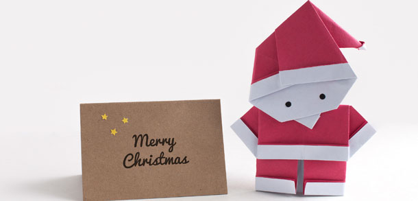 Origami Santa standing next to a Christmas card
