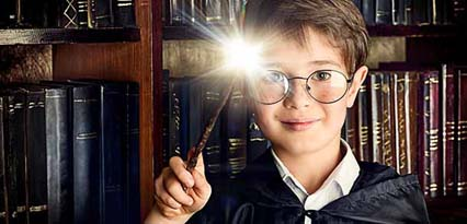 A young wizard with cloak and glasses holds a wand with a light at the end in front of bookshelves filled with old books.