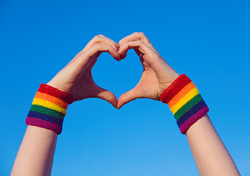Two hands making a heart shape together wearing rainbow wrist bands against a blue background
