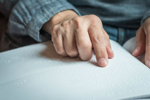 Mans hand moves over braille text.