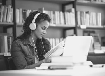 Young woman sat in a library with a book, laptop and headphones
