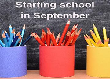 In front of a chalkboard are three pots coloured blue, red and yellow, holding lots of pencils of the same colour, with the wording starting school in September at the top