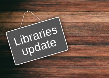 Grey sign pinned to wooden wall, with words written in white saying - libraries update