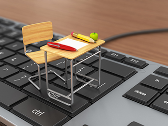 A miniature school desk and chair sitting on a keyboard on a table. On the desk is a miniature pen, pencil, piece of paper and an apple.