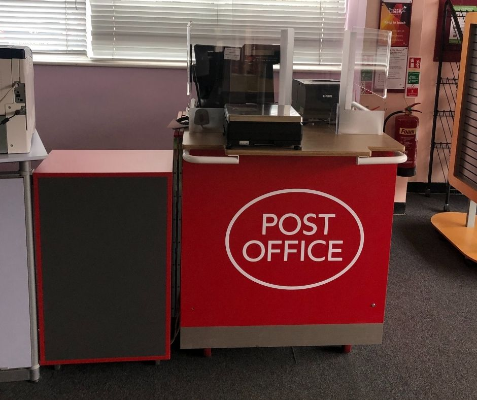Prettygate Library post Office pod desk in front of window. The floor is carpeted and there are various library furnishings round about.