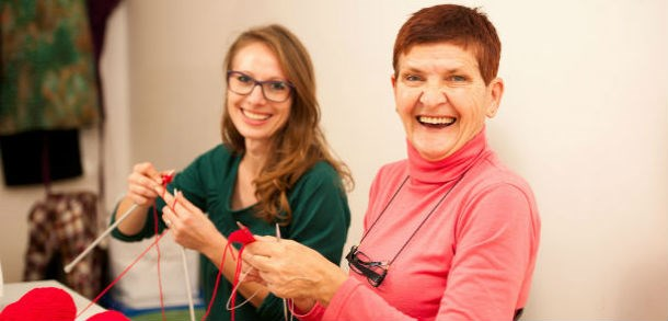 A smiling older and younger woman are sitting together knitting