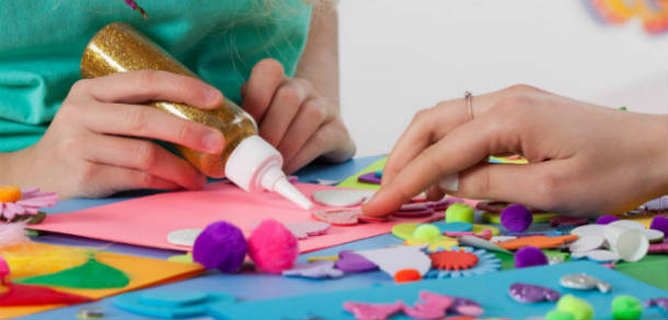 childrens hands gluing and sticking coloured paper