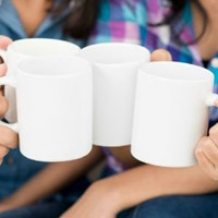 group of hands clinking coffee mugs together