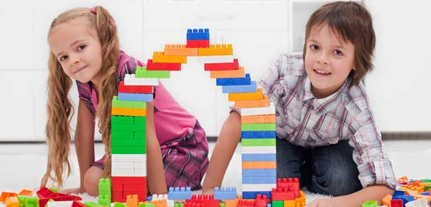 young girl and boy building a tower out of coloured blocks