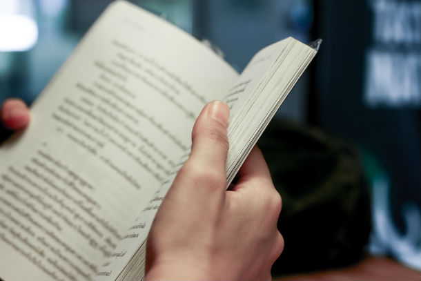 A book is held open by a reader's hands.