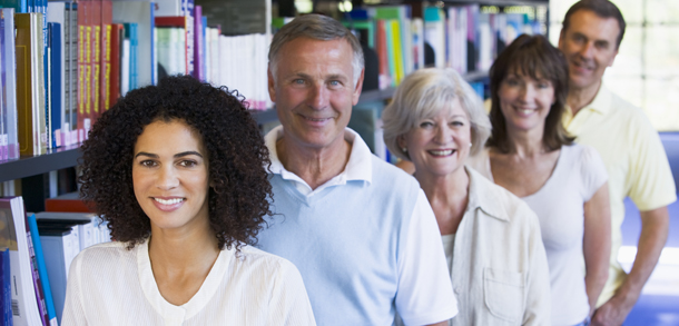 mixed group of people in front of a shelf of books