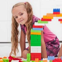boy and girl kneeling by arch built out of blocks