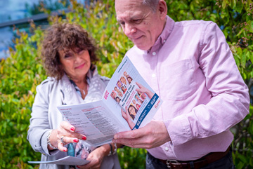 man and woman looking at reading well leaflet