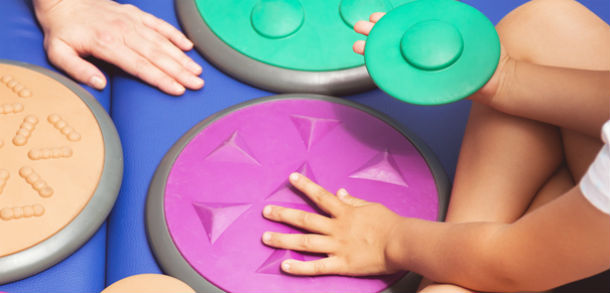 A child's hands hold large coloured discs with different textures on them.