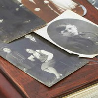 Old black and white photographs lie on top of an old book.