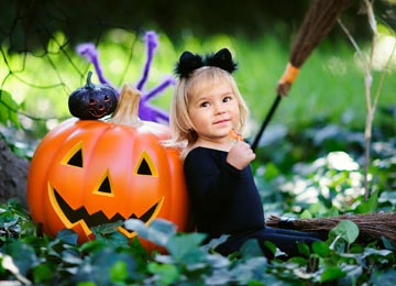 little girl in a halloween costume and a pumpkin